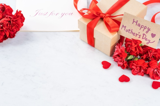 Close up of red carnation with gift box for mother's day greeting