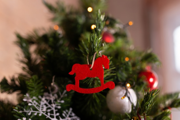 Close up of red christmas horse toy on christmas tree. happy new year and christmas concept. decoration.