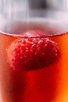 Close up red cocktail with raspberry inside in glass wine.