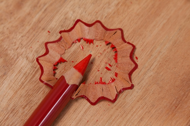 Close-up of red colored pencil with shavings