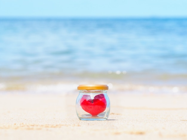 Close up red cushion heart shape in glass bottle on summer beach.