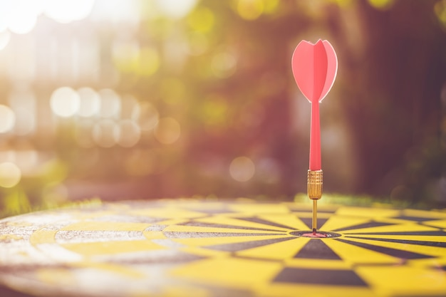 Close up red dart arrow in the center of dartboard. blur and bokeh in sunrise time