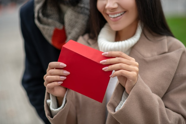Close up of a red envelope being opened while having a love letter inside