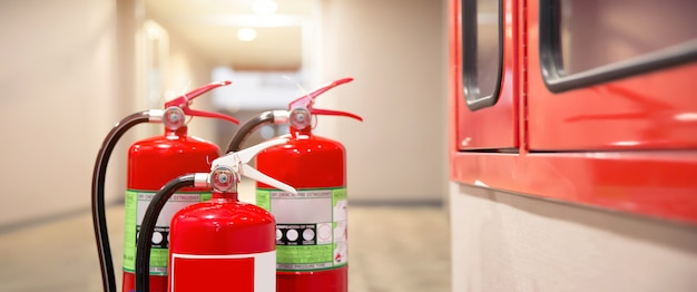Close-up the red fire extinguishers tank at the exit door in the building.