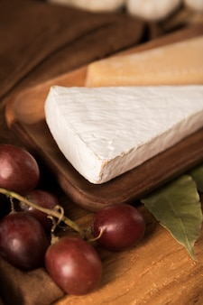 Close-up of red grapes and cheese slices on wooden plate