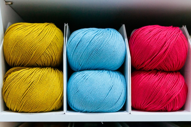 Close up of red green and blue wool yarns on a white shelf