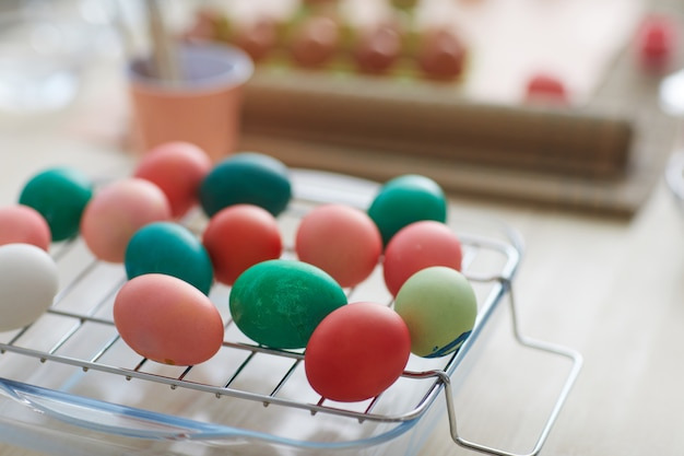 Close up red and green hand-painted easter eggs on drying rack, copy space