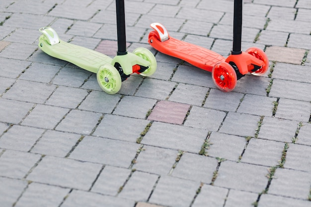 Close-up of red and green kick scooters on cobblestone