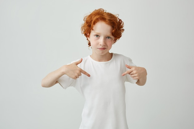 Close up of red haired cute boy with freckles pointing with fingers on white t shirt with serious and confident expression. copy space.