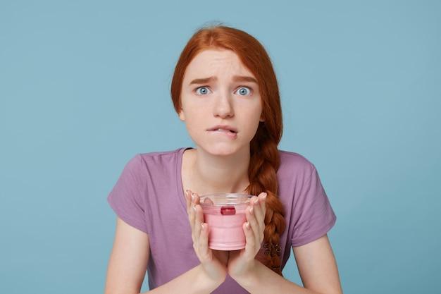 Chiuda in su della ragazza dai capelli rossi che guarda l'obbiettivo morde il labbro, preoccupazioni per la nutrizione