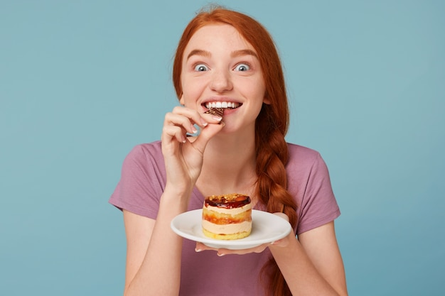 Close up of a red-haired woman eagerly tastes a delicious cake, bites off a piece of chocolate and holds a plate in her hands