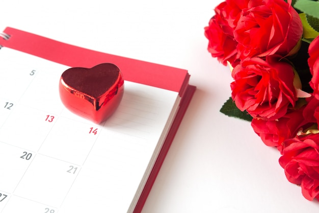 Close up red heart on calendar with red rose on white background, valentine concept