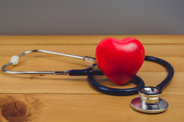 Close up red heart and steythoscope on old wood table