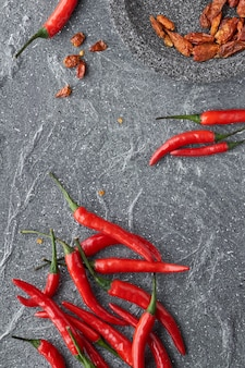 Close-up on red hot chili peppers, fresh and dry, on grey stone, flat lay