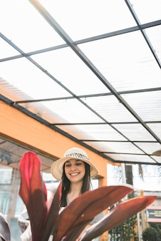 Close-up of red leaves in front of happy woman standing in greenhouse