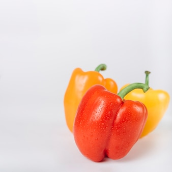 Close-up of red; orange and yellow bell peppers on white backdrop