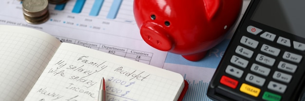 Close-up of red piggy bank terminal and notebook with notations. monthly expenses on rent car food and credit. cash money on desktop. family budget concept