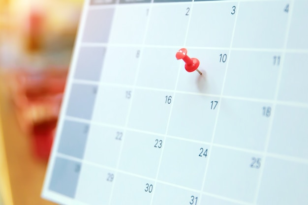 Close-up a red pin on blank desk calendar.