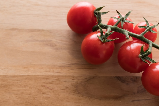 Close up of red ripe organic tomatoes on branch on wooden board. copy space for text.