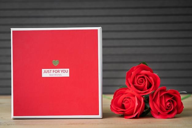 Закройте красные розы и коробку в форме сердца на деревянном фоне, концепцию дня святого валентина с розами и коробку в форме красного сердца