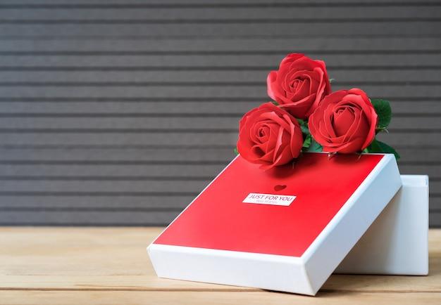 빨간 장미와 나무 배경에 하트 모양의 상자, 장미와 빨간 하트 모양의 상자와 발렌타인 데이 개념을 닫습니다