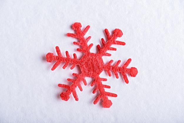 白い背景、クリスマス冬の装飾要素に赤い雪の結晶を閉じる