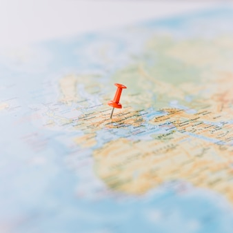 Close-up of a red thumb tack on defocused world map