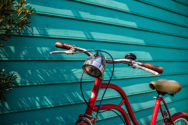 Close-up red vintage bicycle parking on blue wooden wall with copy space
