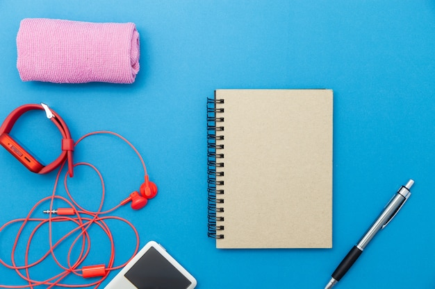 Close up of red watch and red earphones with accessories on blue paper background,fitness background concept.
