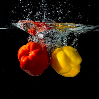 Close-up of red and yellow bell pepper splashing into water