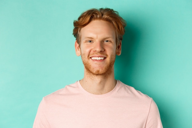 Close up of redhead bearded guy in pink t-shirt, smiling with white perfect teeth and looking at camera, standing over turquoise background