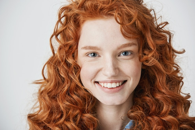 Close up of redhead beautiful woman with freckles smiling.