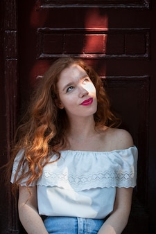 Close-up redhead girl posing in front of a door