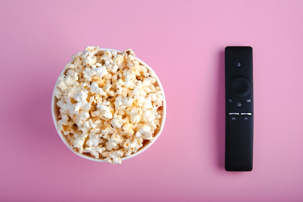 Close-up of remote control and paper cup of popcorn