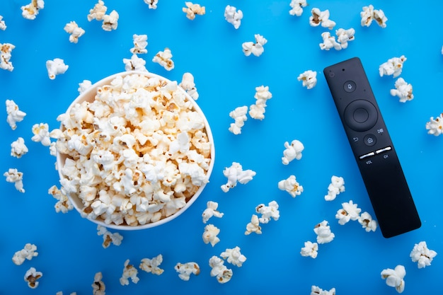 Close-up of remote control and testy warm popcorn viewed from above on blue background