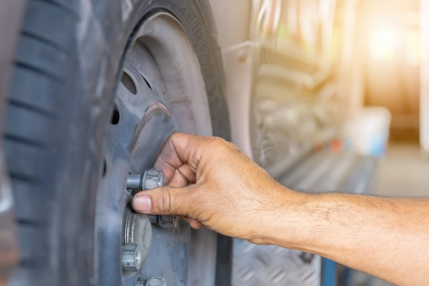 Close up of repair mechanic hands during maintenance work to loosen a wheel nut changing tyre of car