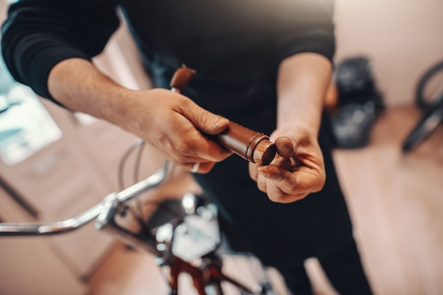 Close up of repairman fixing handlebar grip on bicycle. bicycle workshop interior