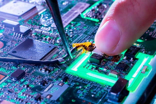 Close up repairmans finger on the green electric circuit board