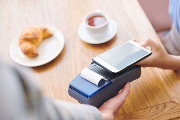 Close-up of restaurant guest sitting at table and using smartphone while paying through mobile payment system