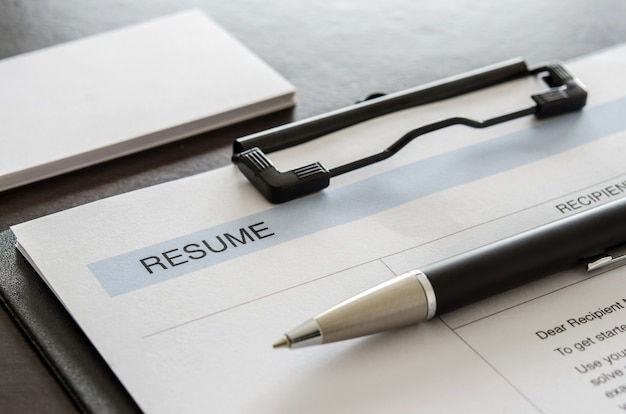 Close-up resume, pen and business card on wooden desk.