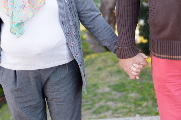 Close-up of retired couple holding hands