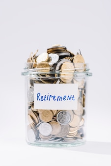 Close-up of retirement glass container full of coins on white background
