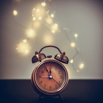 Close up of retro alarm clock on blurred christmas background with light bokeh
