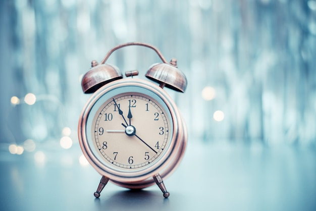 Close up of retro alarm clock on blurred christmas  with bokeh
