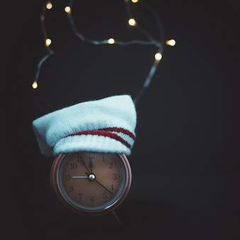 Close up of retro alarm clock in hat on blurred christmas background with garland