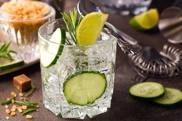 Close up retro glass jars of lemonade with cucumber and mint on wooden table