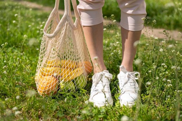 女性の足の近くの再利用可能なバッグをクローズアップ