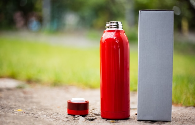 Close-up of reusable steel red thermo bottle for water beside cap and cardboard box for packaging. blurred outdoors background.