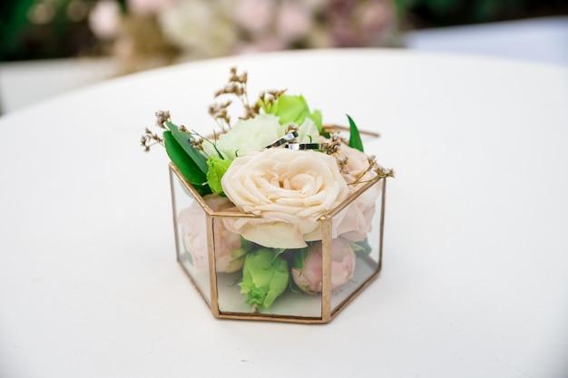 Крупным планом кольца жениха и невесты лежат на подушке из живых бутонов роз в стеклянной коробке на белом столе