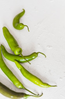 Close-up of ripe green chilies on white background